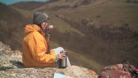 Dziewczyna z długie włosy w żółtej kurtce, szara nakrętka, szkła siedzi na górze, nalewa herbaty napój od termosu, wtedy zdjęcie wideo