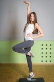 Dziewczyna z długie włosy w gym robi ćwiczeniom Zdjęcia Royalty Free