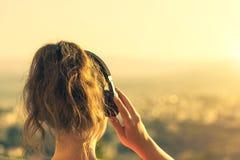 Dziewczyna z długie włosy w hełmofonach na krześle na balkonowym słuchaniu muzyka na zmierzchu tle zdjęcie royalty free