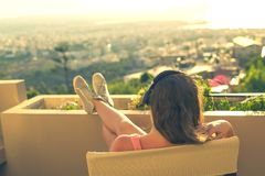 Dziewczyna z długie włosy w hełmofonach na krześle na balkonowym słuchaniu muzyka na zmierzchu tle zdjęcia royalty free