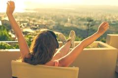 Dziewczyna z długie włosy w hełmofonach na krześle na balkonowym słuchaniu muzyka na zmierzchu tle obraz stock
