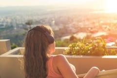 Dziewczyna z długie włosy w hełmofonach na krześle na balkonowym słuchaniu muzyka na zmierzchu tle zdjęcie stock