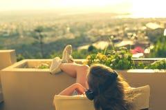 Dziewczyna z długie włosy w hełmofonach na krześle na balkonowym słuchaniu muzyka na zmierzchu tle zdjęcia stock