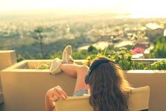 Dziewczyna z długie włosy w hełmofonach na krześle na balkonowym słuchaniu muzyka na zmierzchu tle obrazy stock