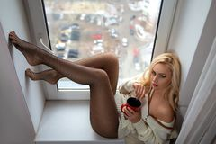 Dziewczyna z doskonalić nogami w pantyhose pozuje na windowsill obrazy royalty free