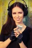 Dziewczyna z Dużymi hełmofonami i Mądrze telefonem na Grunge tle Obrazy Stock