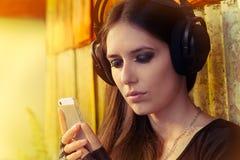 Dziewczyna z Dużymi hełmofonami i Mądrze telefonem na Grunge tle Zdjęcia Royalty Free