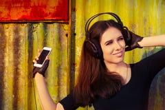 Dziewczyna z Dużymi hełmofonami i Mądrze telefonem na Grunge tle Obraz Stock