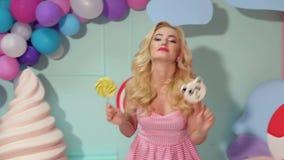 Dziewczyna z dużymi lizakami w jej rękach tanczy zabawę i ma w jaskrawym pokoju zbiory