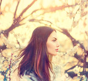 Dziewczyna z długim podmuchowym włosy w wiosna ogródzie Zdjęcia Royalty Free