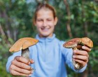 Dziewczyna z dziką pieczarką zakłada w lasowej ostrości na pieczarce Zdjęcia Stock