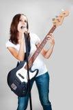 Dziewczyna z elektryczną basową gitarą na szarość Fotografia Royalty Free