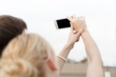 Dziewczyna z facetem trzyma telefon w ich wp8lywy pict i rękach Fotografia Royalty Free