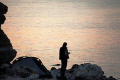 Dziewczyna z filiżanką herbata na skalistym seashore blisko campingowego namiotu Obraz Stock