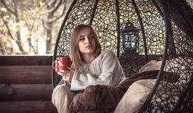 Dziewczyna z filiżanką herbata w wygodnym krześle Obraz Stock