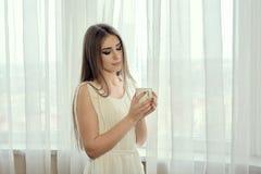 Dziewczyna z filiżanka kawy dla pojęcie projekta atrakcyjnego zamkniętego zbliżenia przyglądający portret w górę kobiety zdjęcia royalty free