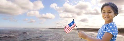 Dziewczyna z flaga amerykańską przeciw linii brzegowej Fotografia Stock