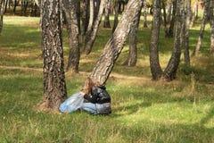 Dziewczyna z grat torbą podnosi w górę grata w lesie, ochrona środowiska, zanieczyszczenie kontrola zdjęcia stock