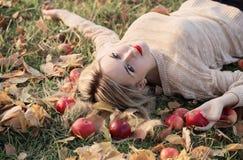 Dziewczyna z jabłkiem kłama na trawie Zdjęcie Royalty Free