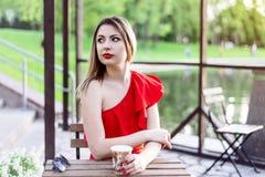 Dziewczyna z jaskrawą pomadką w czerwieni sukni siedzi w kawiarni obrazy stock