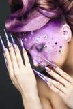 Dziewczyna z jaskrawym purpurowym kreatywnie makeup z kryształami i gwoździami długo Piękno Twarz obrazy stock