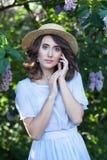 Dziewczyna z jasną skórą i falistym brązu włosy w słomianym kapeluszu w lilym ogródzie w kwiacie Piękny spokojny dziewczyna portr obrazy stock