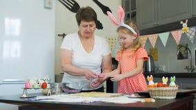Dziewczyna z jej babć wypiekowymi ciastkami na Easter zbiory wideo