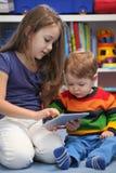 Dziewczyna z jej młodszym bratem używa cyfrowego pastylka komputer Zdjęcie Stock