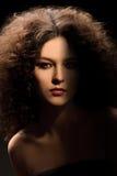 Dziewczyna z kędzierzawą fryzurą, nowożytnym makijażem i carnivore spojrzeniem, zdjęcia royalty free