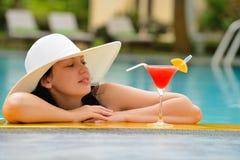 Dziewczyna z koktajlem przy krawędzią pływacki basen zdjęcia stock