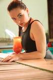 Dziewczyna z koktajlu napojem przy pływackiego basenu krawędzią Zdjęcie Royalty Free