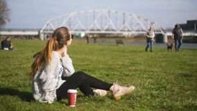 dziewczyna z komórki Młoda powabna kobieta dzwoni z komórka telefonu obsiadaniem na trawie atrakcyjna kobieta zbiory