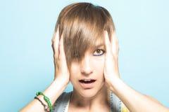 Dziewczyna z krótkim włosy i rękami na ona kierownicza Wyrażenie niespodzianka obraz stock