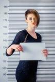 Dziewczyna z krótkim włosy utrzymuje znaka przeciw tłu na wzrost miarze w więzieniu obrazy stock