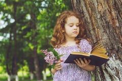Dziewczyna z książką i bukiet bzy blisko wielkiego drzewa Fotografia Royalty Free