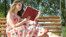 Dziewczyna z książką na ławce w parku zbiory