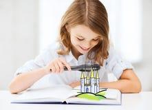 Dziewczyna z książkowy patrzeć roszować przez magnifier Zdjęcie Royalty Free