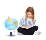 Dziewczyna z kulą ziemską i książką Fotografia Stock