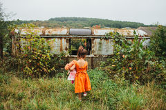 Dziewczyna z lali stojakami blisko starej przyczepy Obrazy Stock