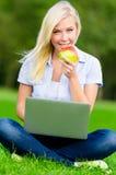 Dziewczyna z laptopem i czerwieni jabłczany obsiadanie na trawie Fotografia Royalty Free