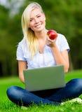 Dziewczyna z laptopu i jabłka obsiadaniem na trawie Zdjęcia Stock