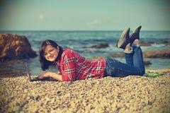 Dziewczyna z laptopu lying on the beach na plaży Fotografia Royalty Free