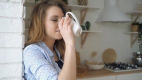 Dziewczyna z luźnym włosy pije herbacianych uśmiechy opiera na ścianie z cegieł zbiory