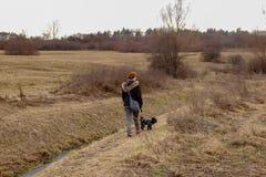 Dziewczyna z małego psa spacerem blisko rzeki obrazy stock