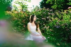 Dziewczyna z marzy spojrzeniem w białym smokingowym obsiadaniu obraz stock