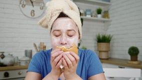 Dziewczyna z maską na twarzy gryźć hamburger w kuchni i żuć pojęcia niezdrowy jedzenie zbiory wideo
