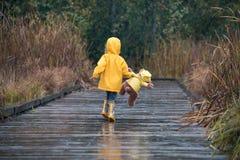 Dziewczyna z misiem chodzi w w dopasowywanie żółtych deszczowach fotografia royalty free