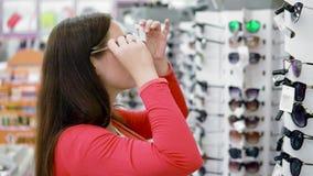 Dziewczyna z ogonem na jej włosów stojakach wśród rzędów z okularami przeciwsłonecznymi Próbuje dalej eleganckich szkła i patrzej zbiory wideo
