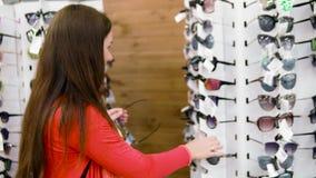 Dziewczyna z ogonem na jej włosów stojakach wśród rzędów z okularami przeciwsłonecznymi Próbuje dalej eleganckich szkła i patrzej zdjęcie wideo