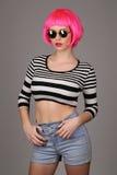 Dziewczyna z okregów okularami przeciwsłonecznymi i różowym włosy z bliska Szary tło Fotografia Stock